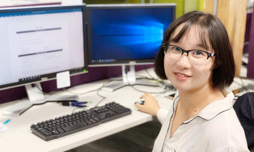 Woman at computer, she is turned facing the camera smiling